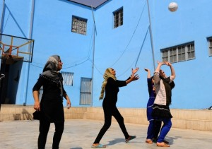 Women playing volleyball inside an Afghan prison for women in Herat. The prison was built in cooperation with an Italian NGO and offers skills training to prepare women for a life outside prison. Image by Aref Karimi/AFP/Getty Images
