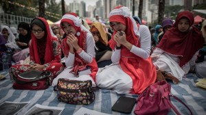 Indonesian migrant workers hold a prayer vigil in Hong Kong for the two women brutally murdered, whose bodies were found earlier this month. Image by Philippe Lopez/AFP