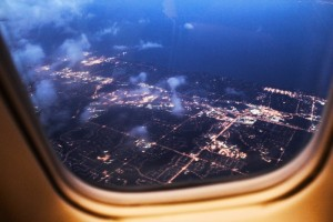 The image shown is that of an aerial view of a city landscape at night through the window of an airplane. Lights can be seen against a dark blue, night sky. Several clouds are seen on the left hand side of the image.