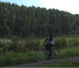 A woman is pictured riding a bike on a road, against a backdrop of green forests and fields.